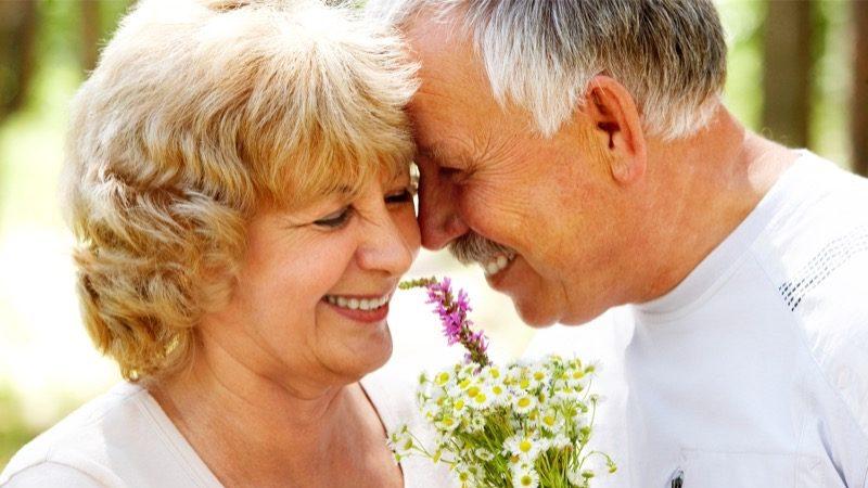 Motiv: Ældre ægtepar tæt sammen. De ler fortroligt.