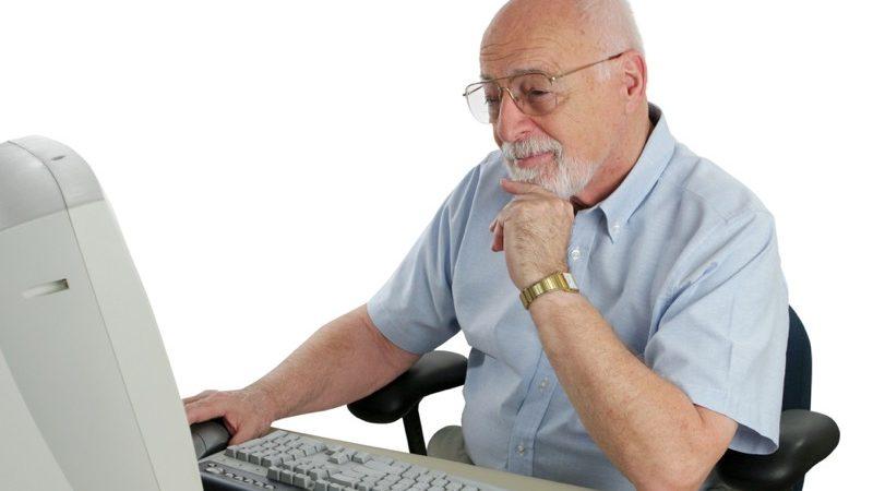 Motiv: Ældre mand sidder ved en gammel computer