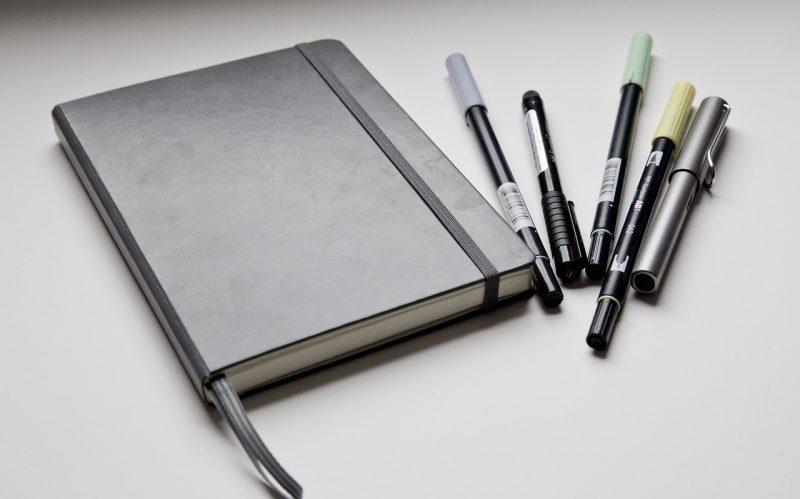 Motiv: Bulletjournal og tuscher på et bord