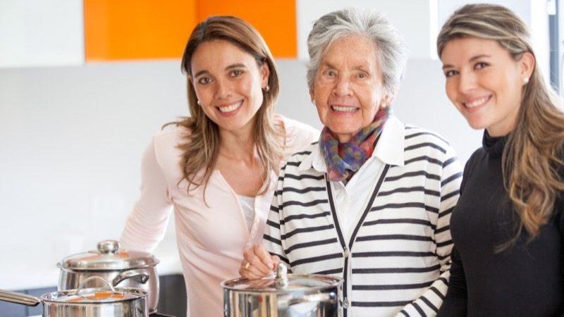 Motiv: Ældre kvinde i køkken flankeret af to yngre kvinder