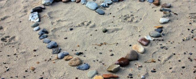 Kærlighed symboliseret af et hjerte af sten på en strand