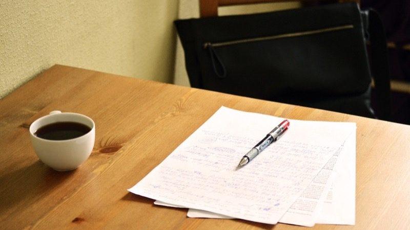 Motiv: Korrekturlæserens borg. Opgave. Ovenpå en rød kuglepen. Ved siden af en kop kaffe.