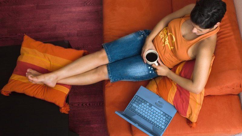 Motiv: Kvinde i sofa med bærbar – i fugleperspektiv