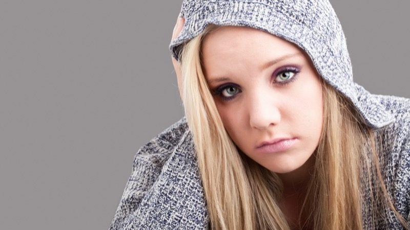 Motiv: Ung pige med grå hættetrøje og mørk øjenmakeup ser trist ind i kameraet
