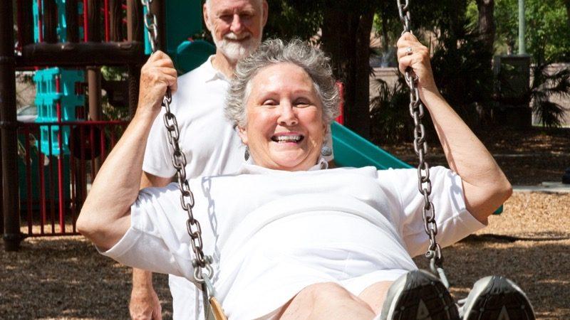 FOSS. Motiv: En ældre mand skubber en ældre glad kvinde som sidder på en gynge