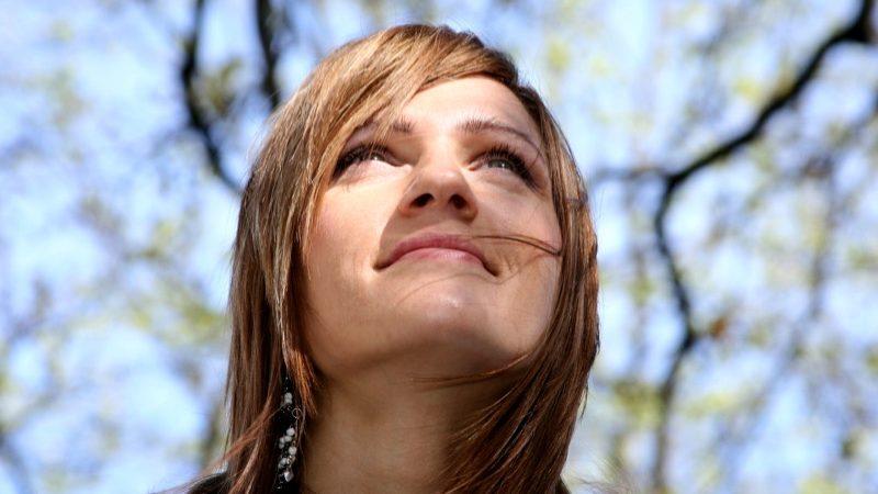 Hovedtropperne. Motiv: Ung kvinde kigger eftertænktsomt op mod en blå himmel