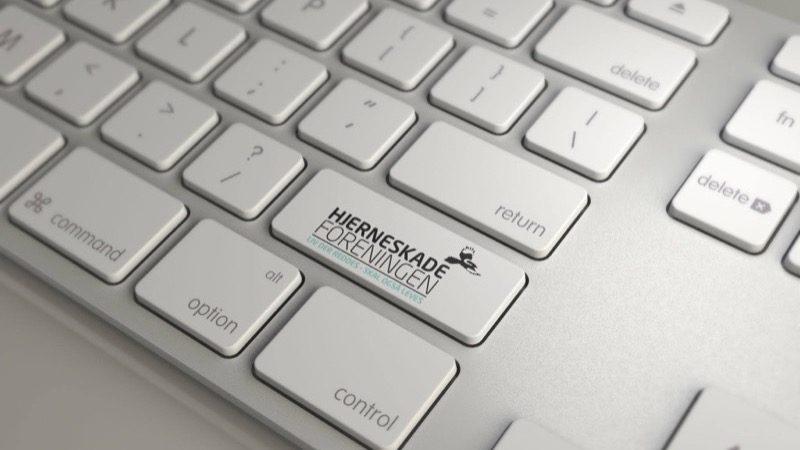 Motiv: Tastatur med Hjerneskadeforeningens logo på Enter-knappen
