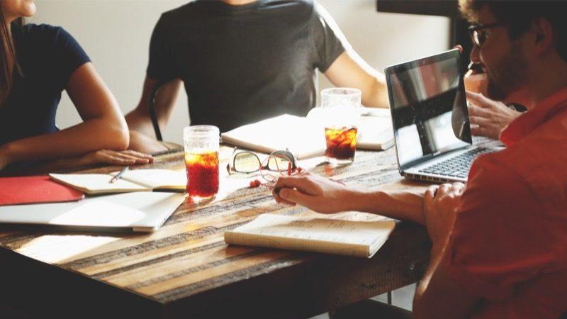 Projekter. Motiv: En gruppe arbejder sammen ved et bord med blokke og laptops