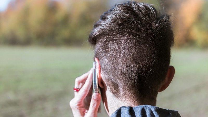 Rådgivning – Motiv: Baghovedet er mørkhåret, korthåret kvinde som taler i telefon