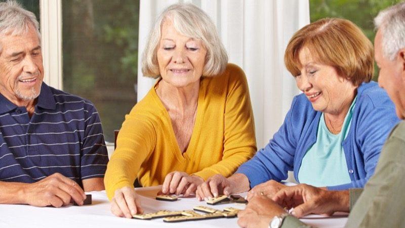 Motiv: Fire mennesker spiller domino sammen