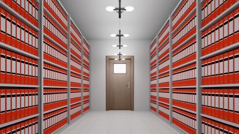 Motiv: Stort hvidt rum med hylder fra gulv til loft fyldt med ens røde ringbind. I enden af rummet er en dør med et vindue i.